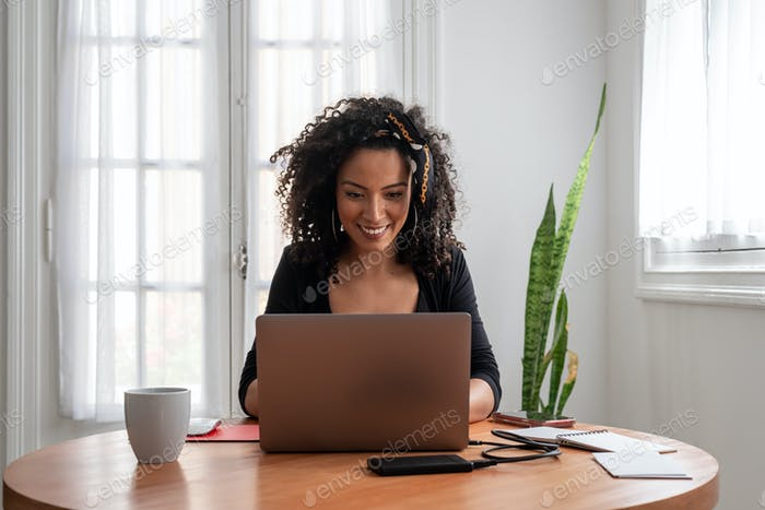 Latin woman working at home with laptop and documents