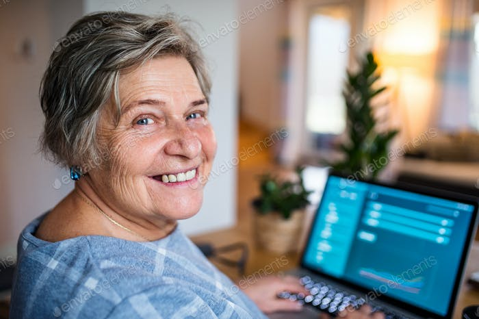 Senior woman with laptop working in home office