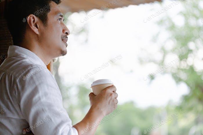 Nahaufnahme des jungen Mannes mit Kaffee zu nehmen am frühen Morgen zu Hause, Sonnenlicht, verschwommen