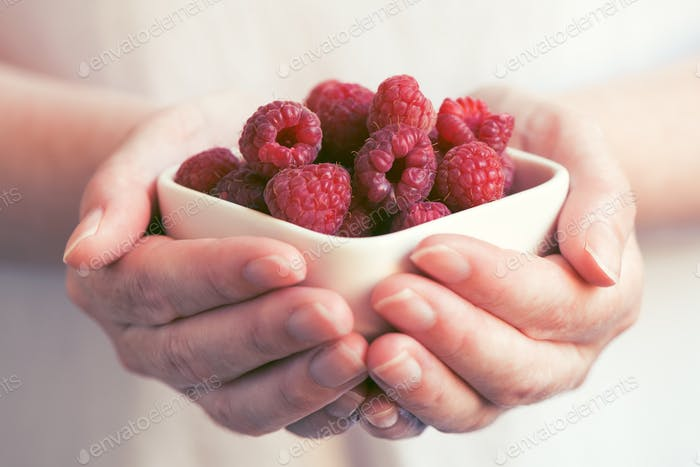Crockery with raspberries in woman hands