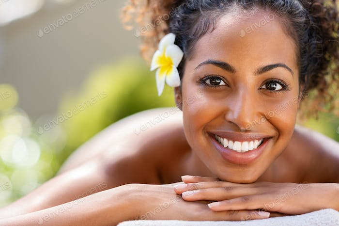 Beauty african woman lying on massage table at spa