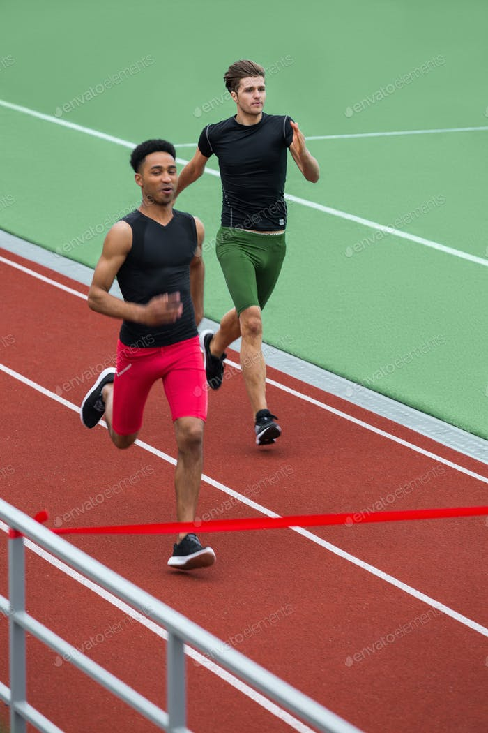 Group of athlete men run on running track outdoors