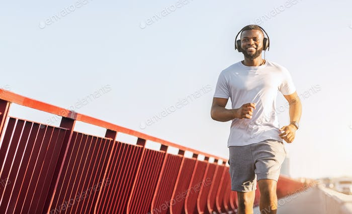 Happy black man running along the bridge, listening to music