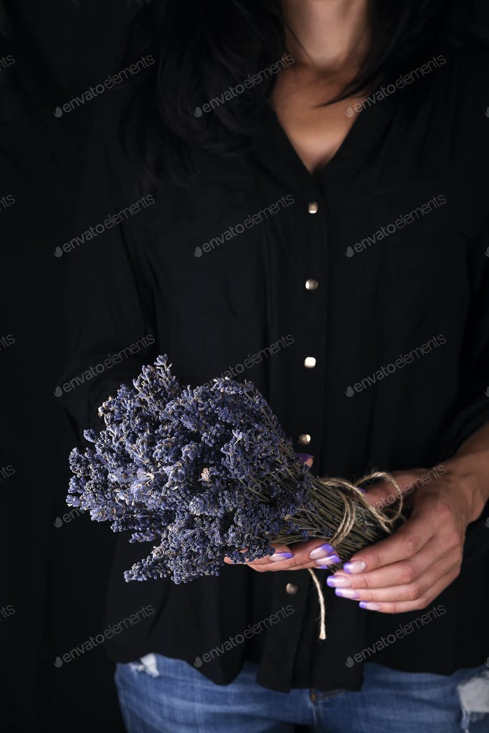 Female florist tying up fresh bouquet with lavender