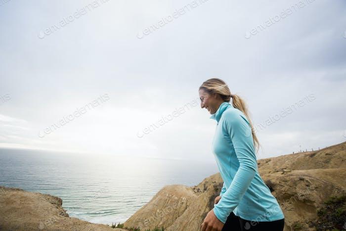 Woman jogging along the coast.