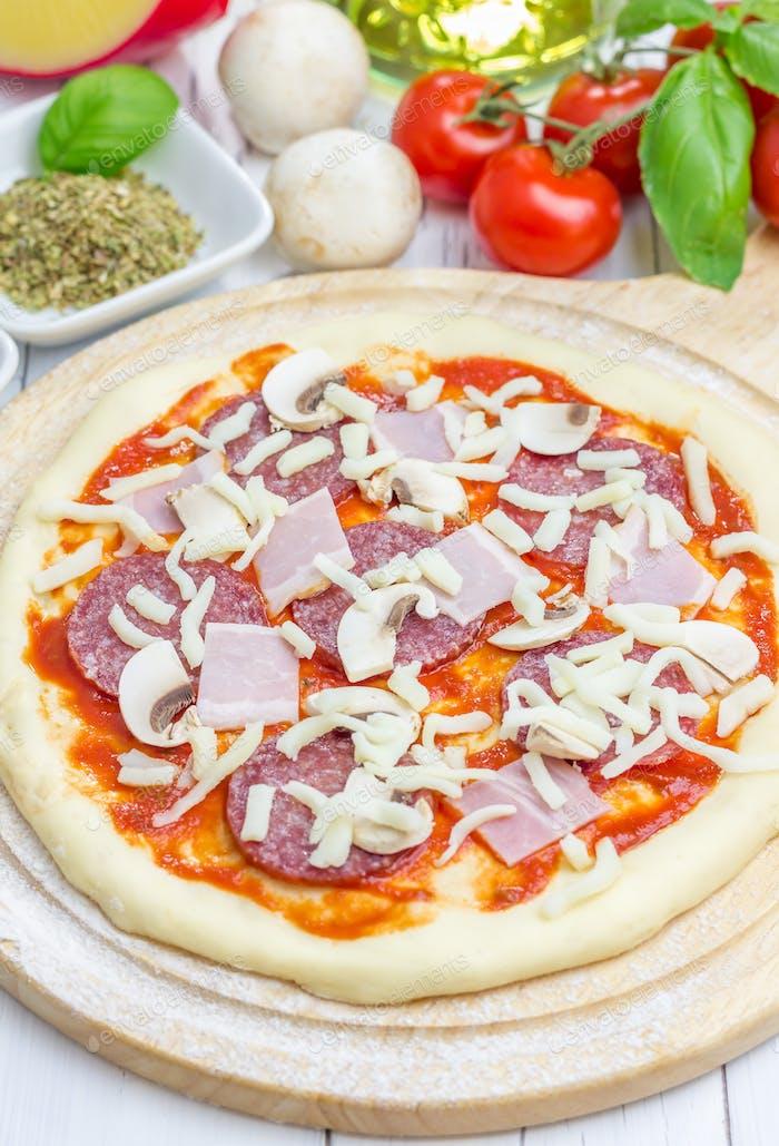 Pizzateig mit Tomatensauce, Salami, Speck, Pilzen und Käse