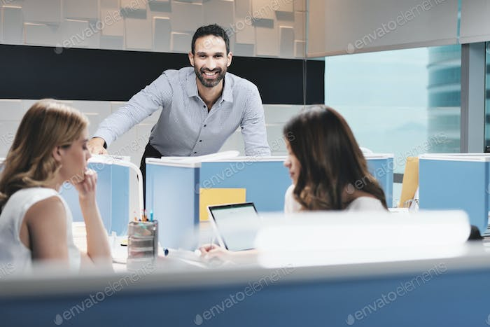 Portrait Of Happy Businessman Smiling At Camera In Coworking Office