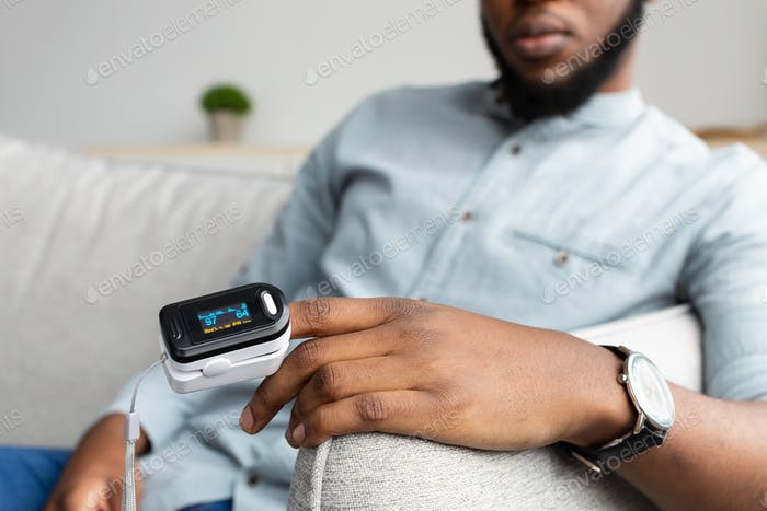 Black Man With Pulse Oximeter Measuring Oxygen Saturation At Home