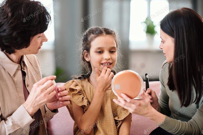 Kleines Mädchen im Kleid trägt nahrhaften Balsam auf die Lippen auf, während es in den Spiegel schaut