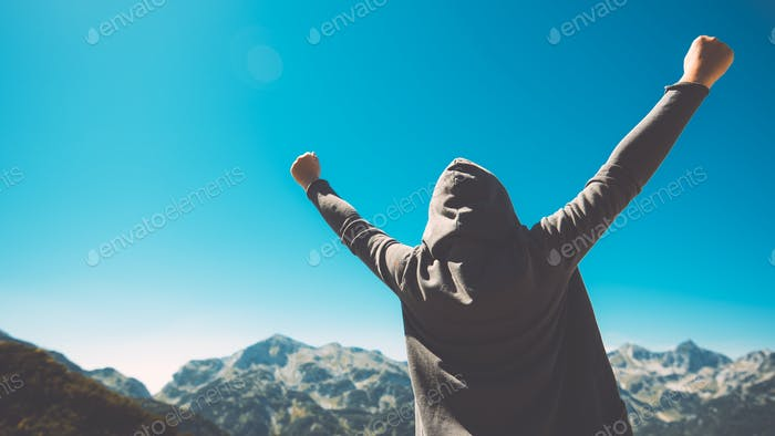 Winning and success. Victorious female person on mountain top.