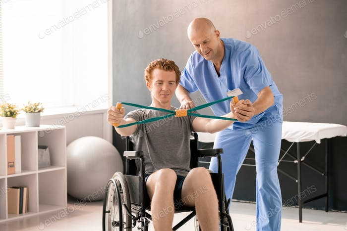 Mature clinician in blue uniform supporting hand of young patient in wheelchair