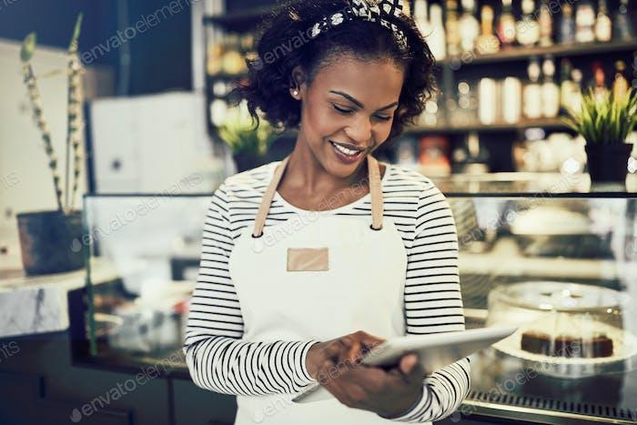 Lächelnder afrikanischer Café-Besitzer arbeiten mit einem digitalen Tablet