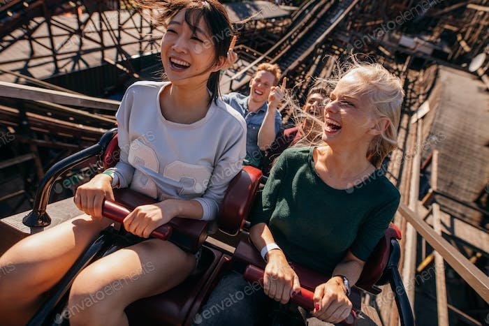 Smiling young people riding a roller coaster