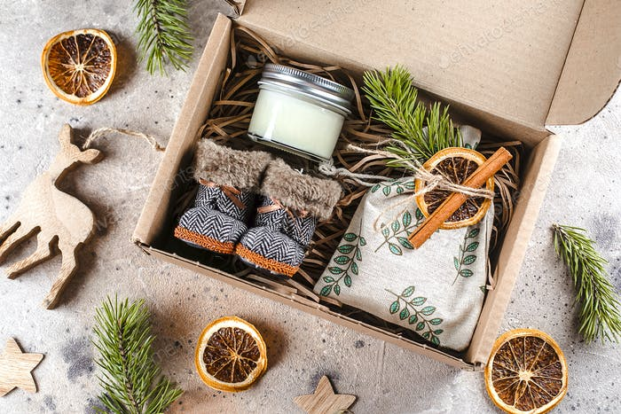 Holiday christmas gift box with cozy items textile pouch, candle, small boots. Care package concept