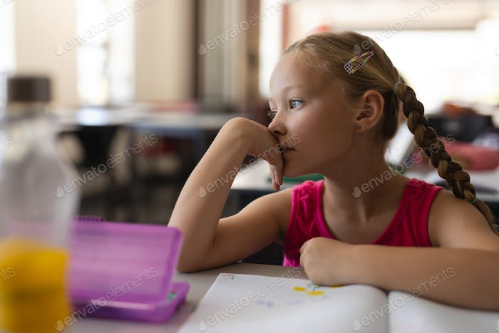 Close-up of thoughtful schoolgirl leaning on desk and looking away in classroom of elementary school