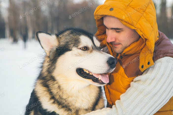 Man with dog husky malamute winter park