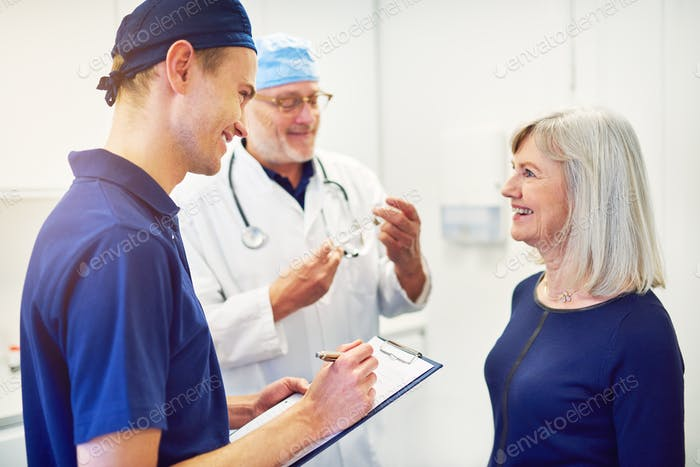 Doctor consulting woman while smiling assistant writing in tablet