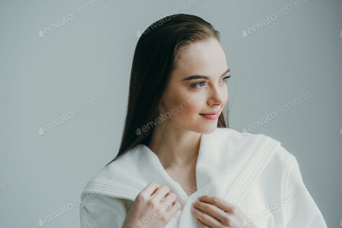 A woman in a white coat touches her hair. The concept of spa cosmetology.