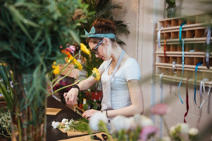Woman florist making bouquet with white flowers in the shop