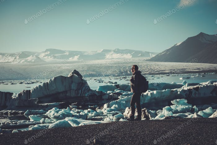 Woman explorer lookig at Jokulsarlon lagoon, Iceland.