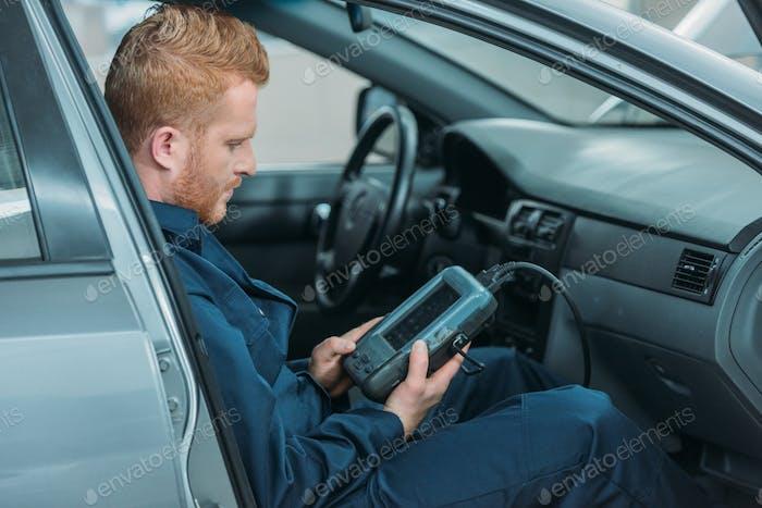 Automechanic sitzt in einem Auto, mit einem Auto-Diagnosegerät