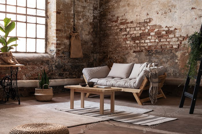 Wooden table on rug in front of beige settee in bright loft inte