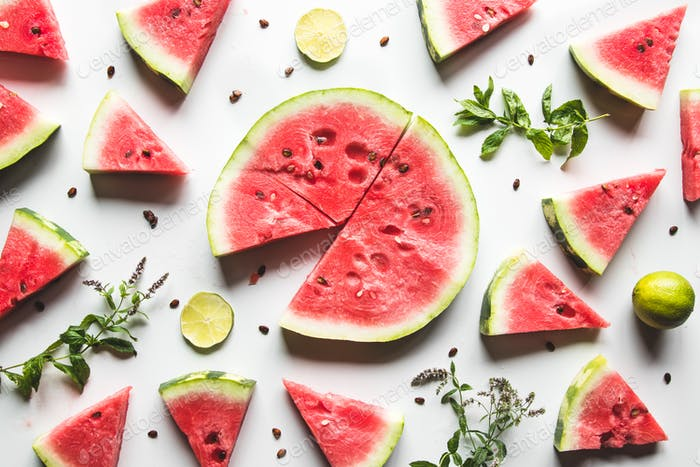 Red slices of ripe watermelon with mint leaves and lime slices on a white background. Top view