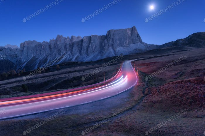 Blurred car headlights on winding road at night