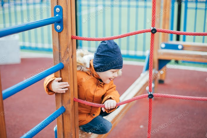 Little boy 5 years old in an orange jacket at the playground. Children's leisure outdoors, games