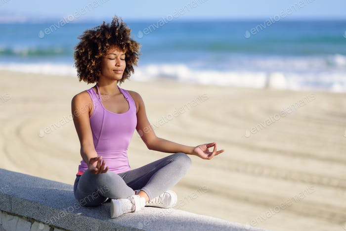 Black woman, afro hairstyle, in lotus asana with eyes closed in the beach