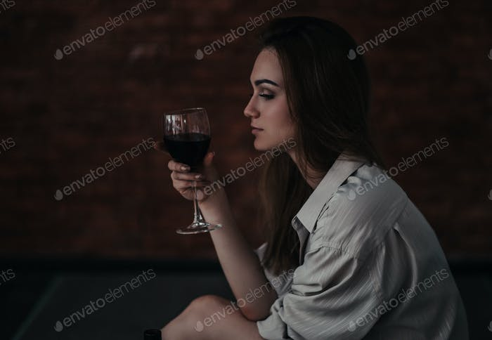 beautiful sad woman sitting on floor in shirt, hold wine she is upset, alone, nobody loved, without