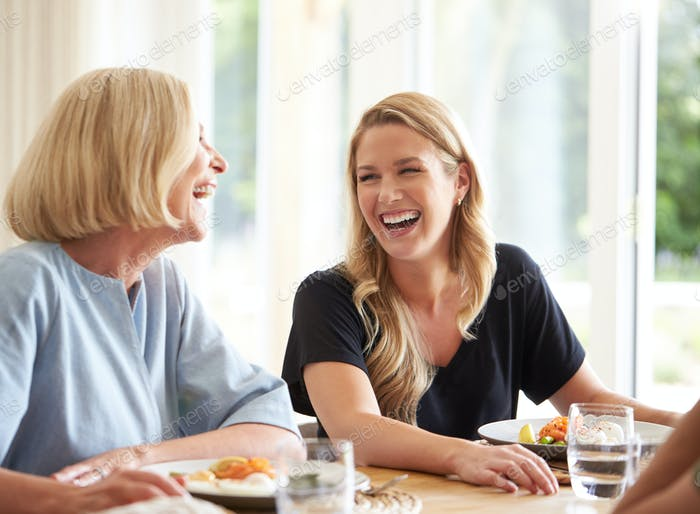Family With Senior Mother And Adult Daughter Eating Brunch Around Table At Home Together