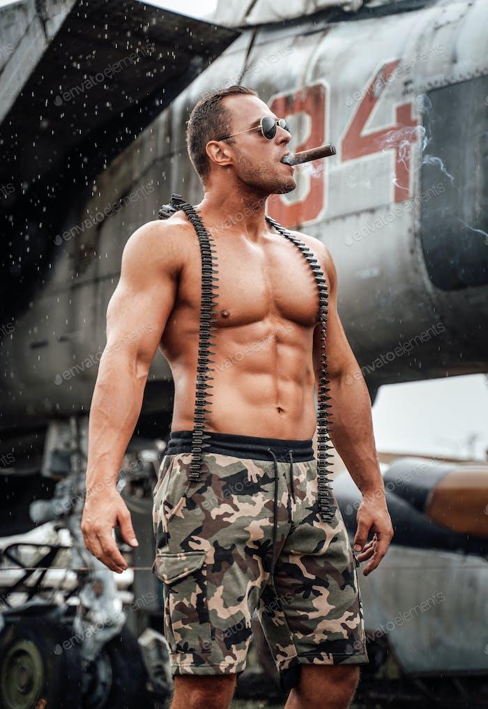 Strong military guy with naked torso smoking cigar at airport
