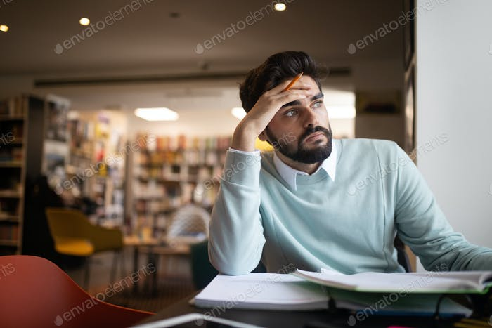 People, education, studying, exams and school concept - tired student learning in library