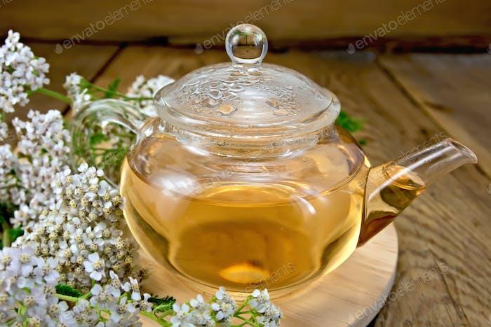 Tee mit Schafgarbe in Glas-Teekanne an Bord