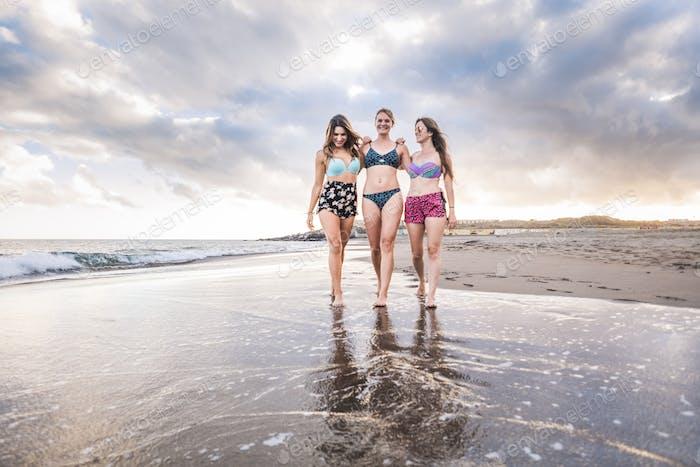 drei fröhliche schöne Damen junge Frauen, die freundschaftlich am Ufer spazieren gehen