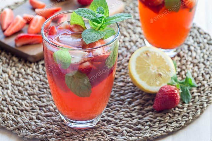 Homemade iced tea with strawberries and mint on a wooden table,