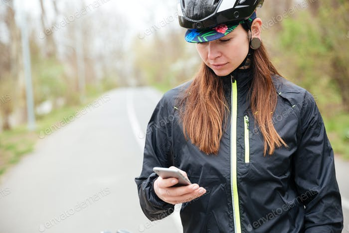 Thoughtful woman in bicycle helmet using cell phone