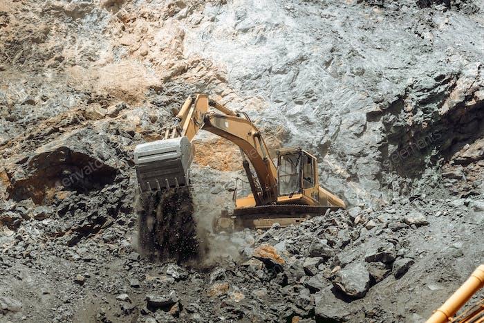 Industrial track type excavator working on highway construction site.