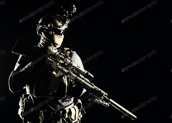 Army marksman with sniper rifle in darkness