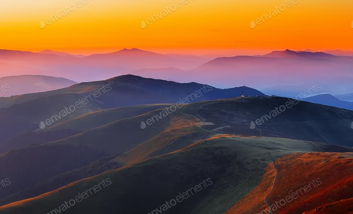 winding road through meadows of  mountain range at sunset