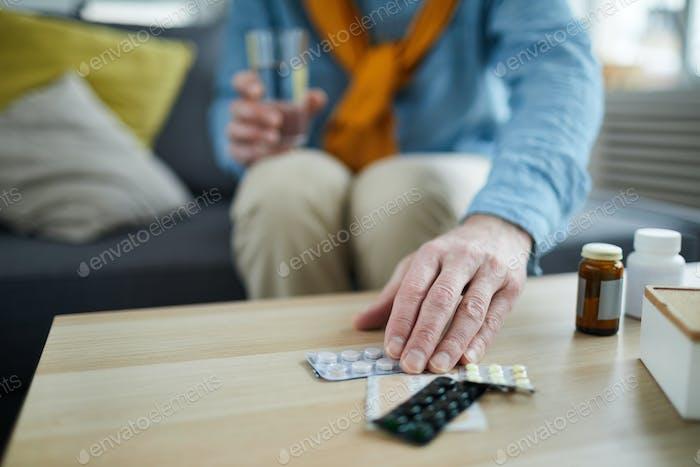 Unrecognizable Man Taking Pills