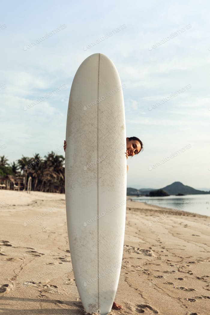 smiling naked girl or woman hiding behind white surfboard on sandy sunny beach