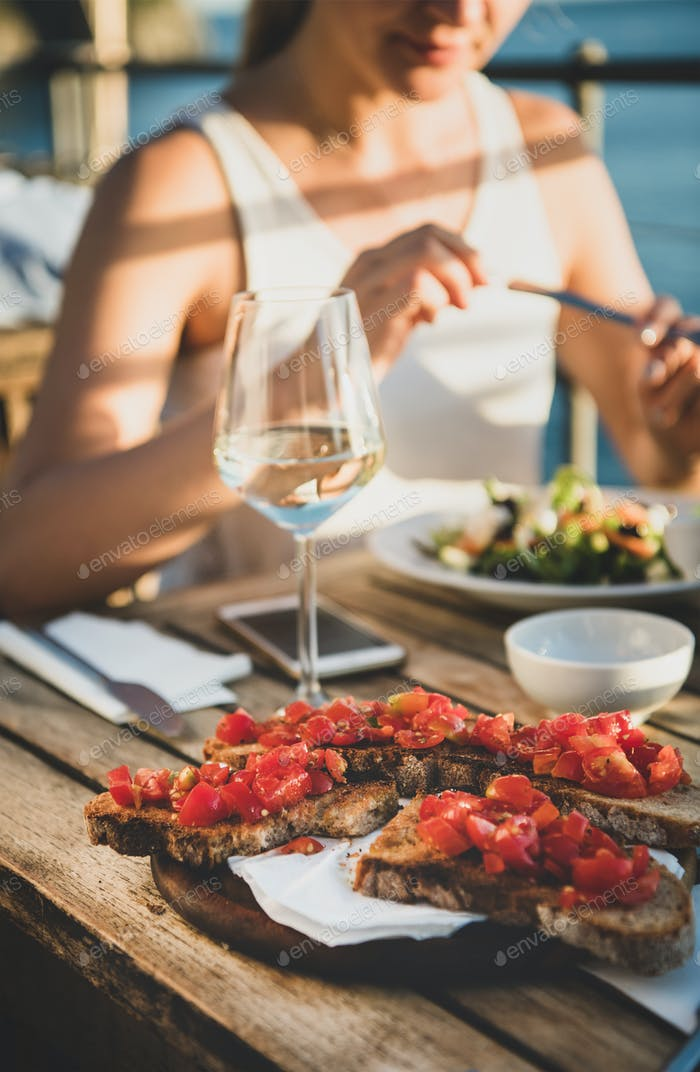 Young woman eating salad and brischetta in Italy in summer