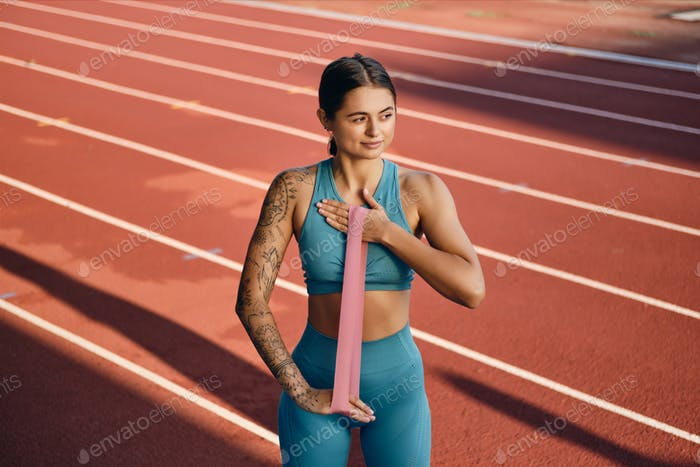 Pretty girl in stylish sportswear dreamily stretching with rubber band during workout on stadium