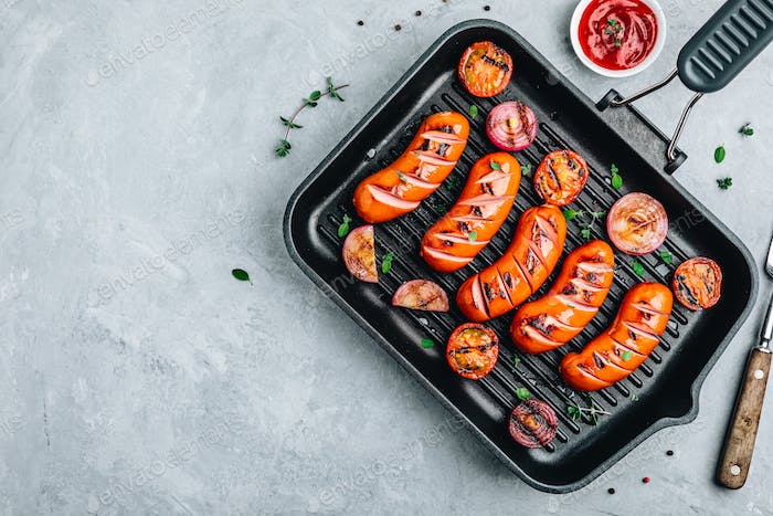 Grilled sausages and vegetables in cast iron pan.