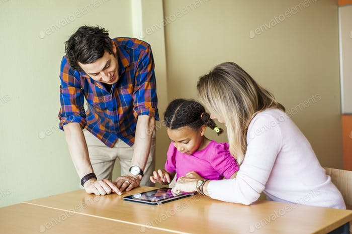 Teachers with girl painting on tablet computer in classroom