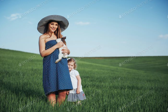 Happy mother and baby with rabbit on hands in field