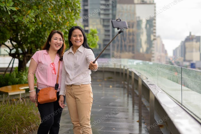 Two mature Asian women together against view of the city