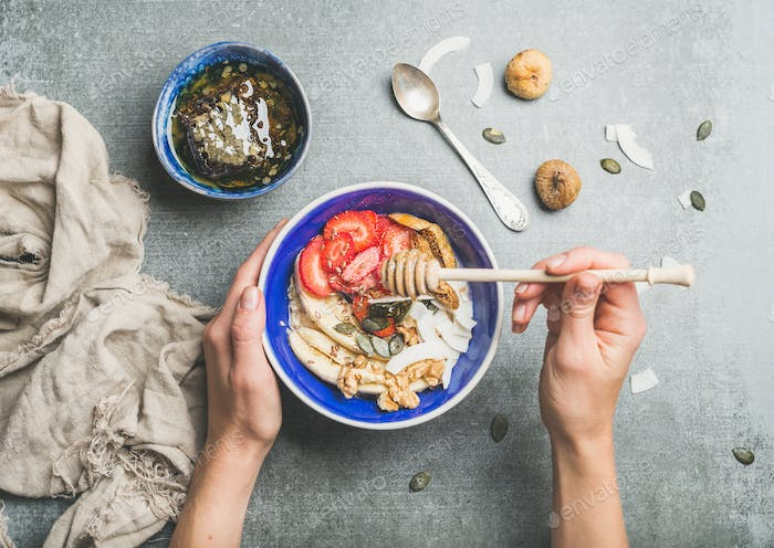 Blue bowl with healthy vegetarian breakfast ingredients in woman's hands